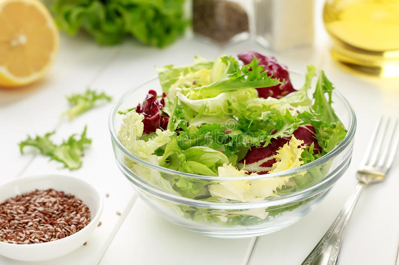 Mixed salad of iceberg, radiccio, endive, cabbage with flax seeds, oil and lemon on white wooden background. royalty free stock image