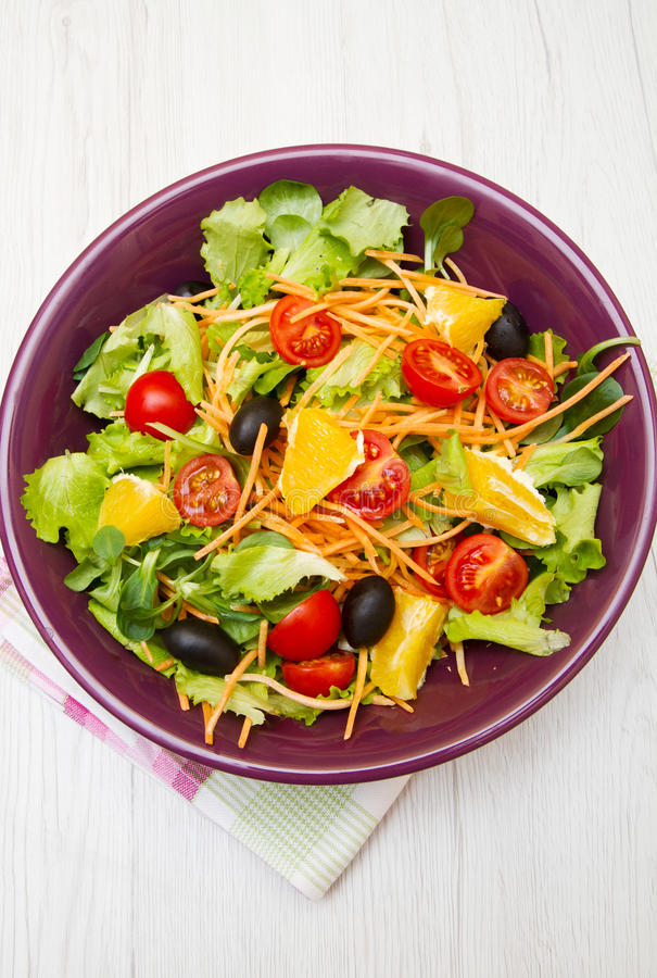 Mixed salad with tomatoes in purple bowl royalty free stock images