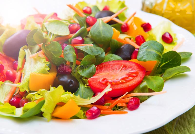 Mixed salad with tomatoes in white plate on wood table royalty free stock photo