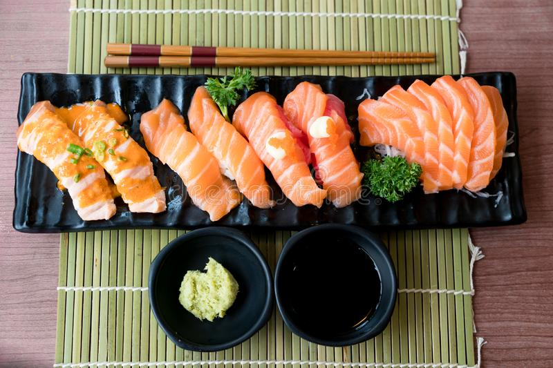 Mixed salmon sushi and sashimi on black plate along with Japanese sauce and green leaf decoration, Japanese food, close up at royalty free stock images