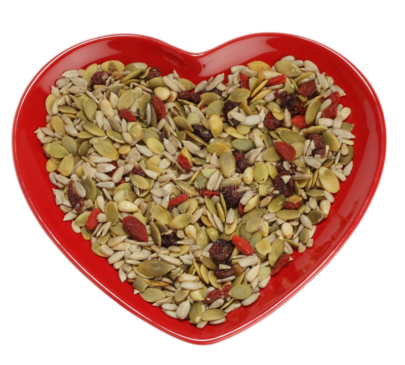 Mixed seeds cereal for healthy breakfast. Or snacking in heart shape plate, over white stock photography