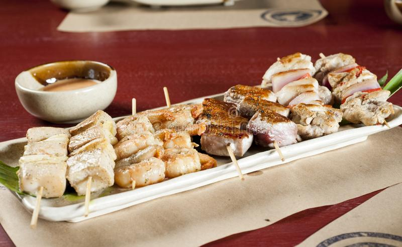 Mixed skewers, chicken meat, fish and cow. Mixed skewers, chicken meat, fish and cow Peruvian royalty free stock photos