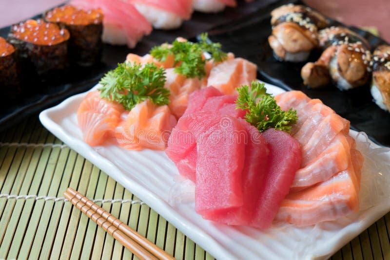 Mixed sliced fish sashimi in white plate. Sashimi Salmon and Tuna set with Tuna, flying fish roe caviar and Foie Gras closeup. stock images