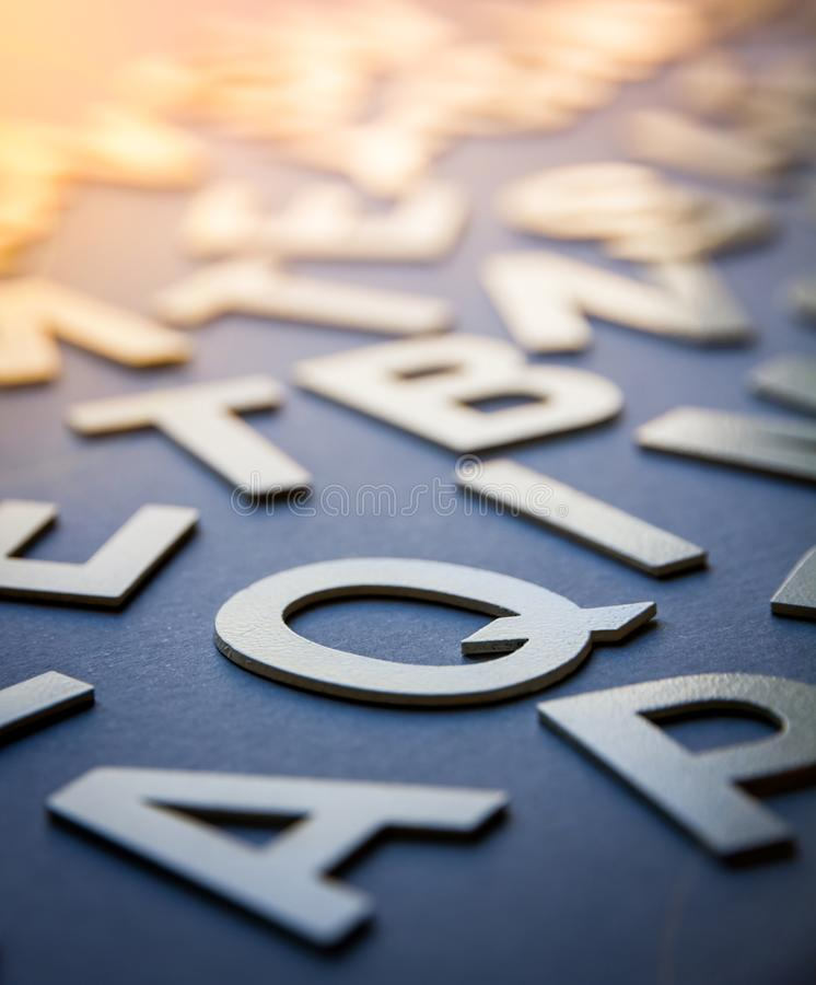 Mixed letters pile closeup photo. Mixed solid letters pile closeup photo. Education background concept stock photography