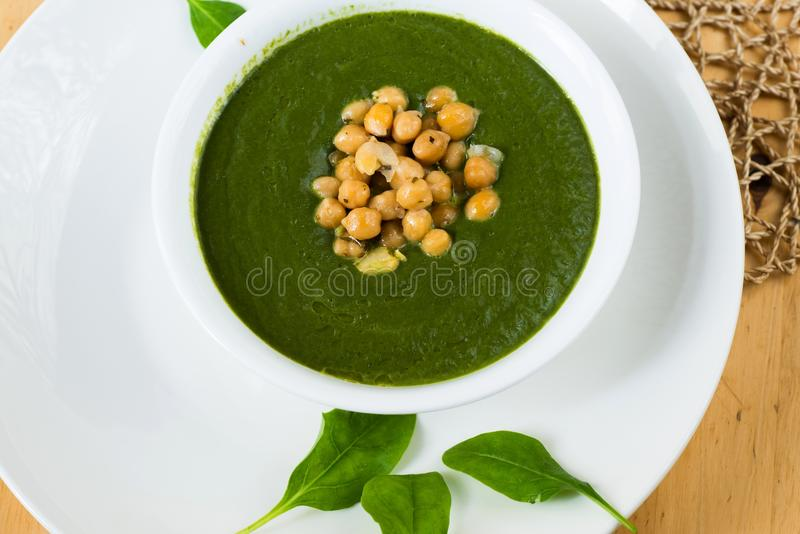 Mixed spring spinach with chickpeas and herb. Mixed spring spinach with chickpeas and herb in bowl on white plate with spinach leaf stock image