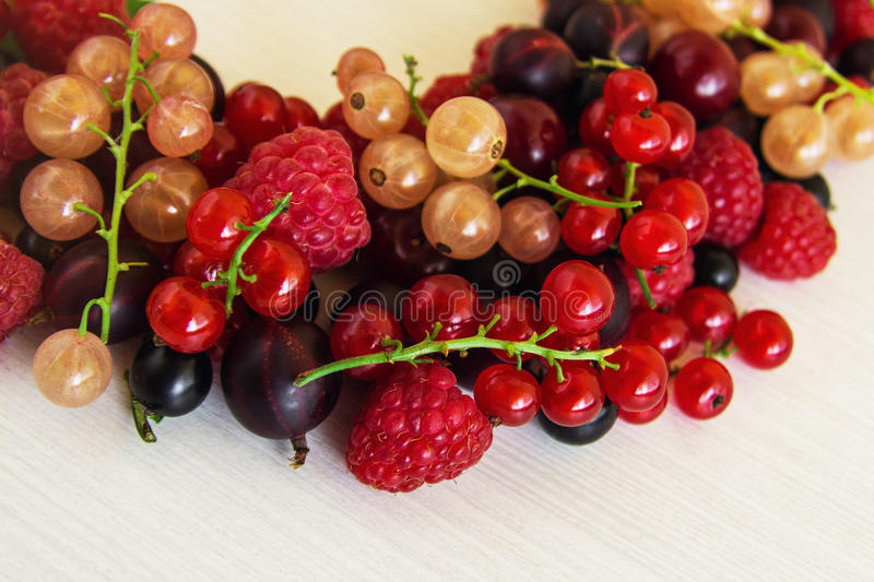 Mixed summer berries raspberry, blackcurrant, redcurrant, white currant, gooseberry, cherry on the white background. Mixed summer berries raspberry royalty free stock images