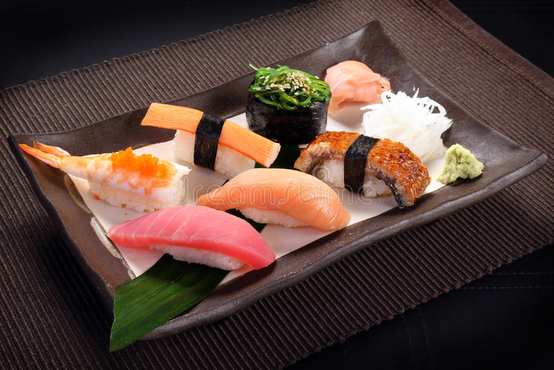 Mixed sushi set with wasabi on ceramic dish, sweet boiled shrimp stock images