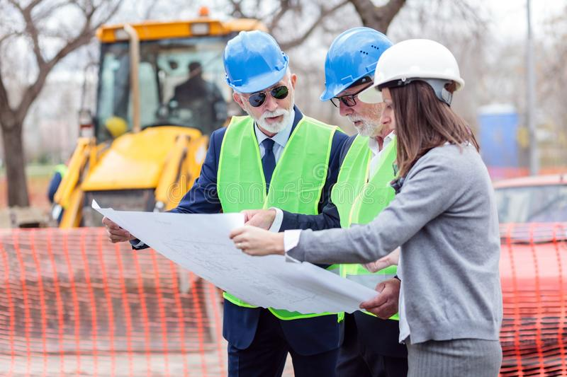 Mixed team of engineers meeting and discussing blueprints while visiting construction site site stock photo