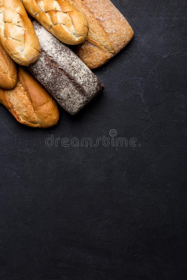 Mixed variety of breads on dark table. Top view with copy space stock images