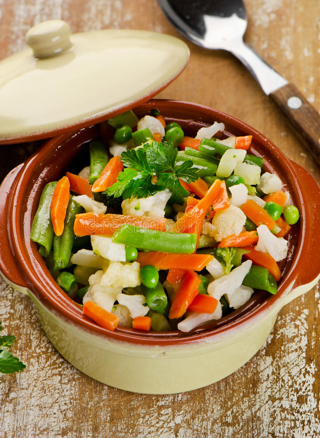 Mixed vegetables in a bowl on wooden board stock image