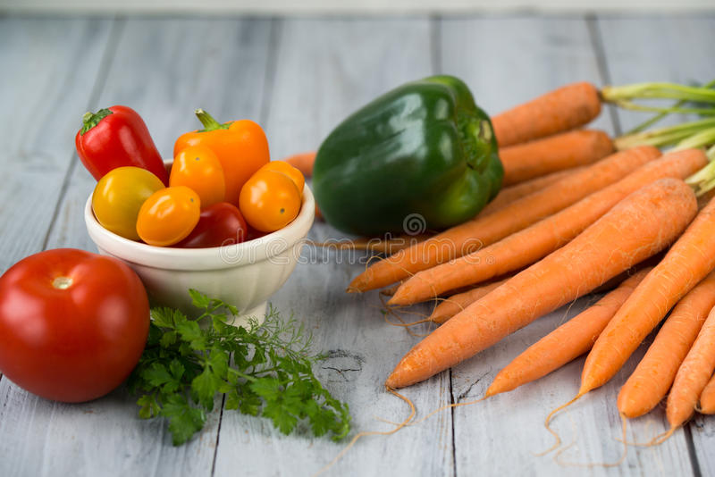 Mixed vegetables. Carrots, paprika, cherry tomatoes in a bowl, tomato and herbs on a kitchen wooden table stock photos