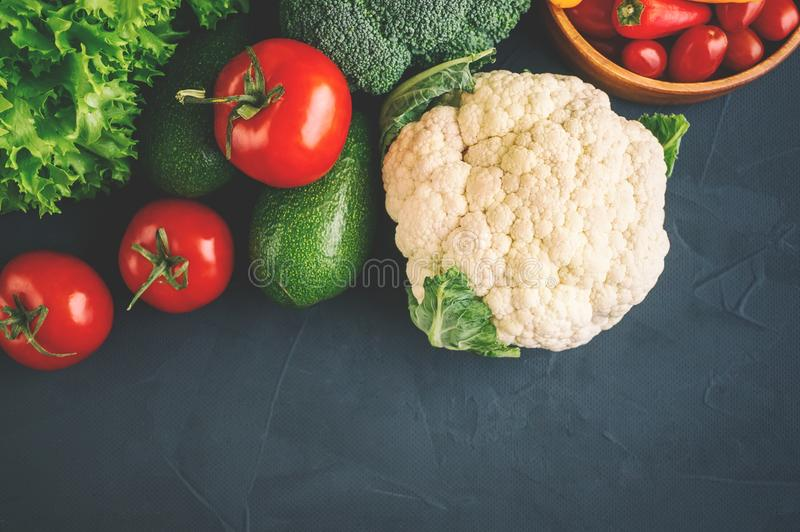 Mixed vegetables of cauliflower and broccoli, garlic, green onions, tomatoes and green peas on a wooden background in stock photo
