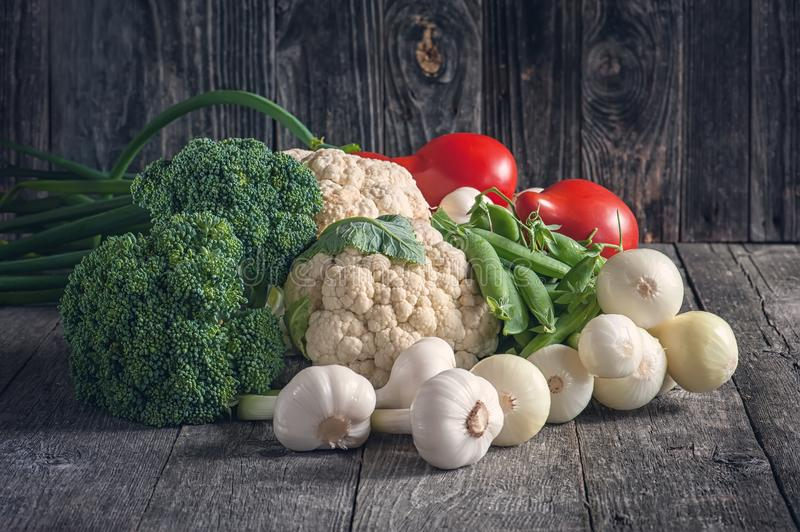 Mixed vegetables of cauliflower and broccoli, garlic, green onions, tomatoes and green peas on a wooden background in rustic style royalty free stock images