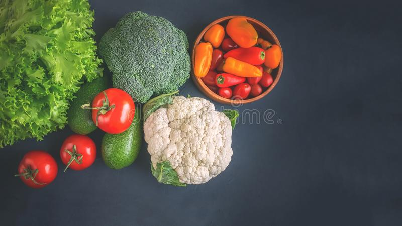 Mixed vegetables of cauliflower and broccoli, garlic, green onions, tomatoes and green peas on a wooden background in rustic style stock photo