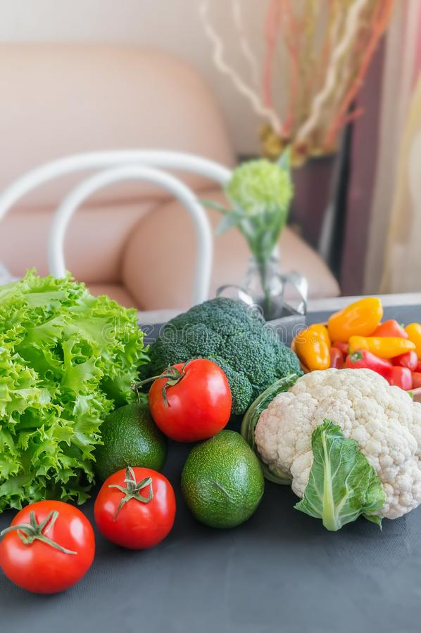 Mixed vegetables of cauliflower and broccoli, garlic, green onions, tomatoes and green peas on a wooden table in the kitchen to pr royalty free stock photos
