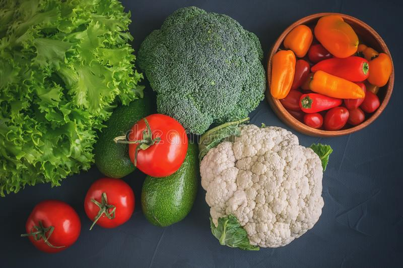 Mixed vegetables of cauliflower and broccoli, garlic, green onions, tomatoes and green peas on a wooden background in rustic style stock image