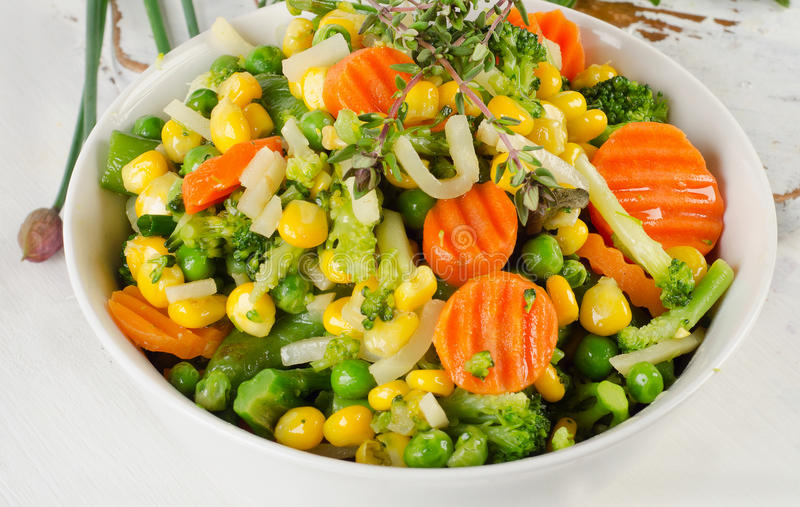 Mixed vegetables with fresh herbs in white bowl. royalty free stock image