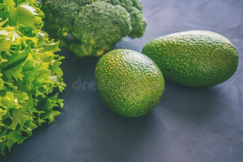 Mixed vegetables of lettuce, broccoli and avocado on a wooden table in the kitchen for preparation of vegetarian dishes. royalty free stock images