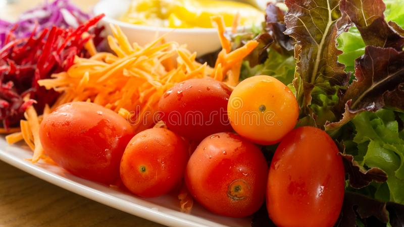 Mixed vegetables salad on white plate with caesar salad sauce, tomatoes, red and green oak, crispy bread topping stock images