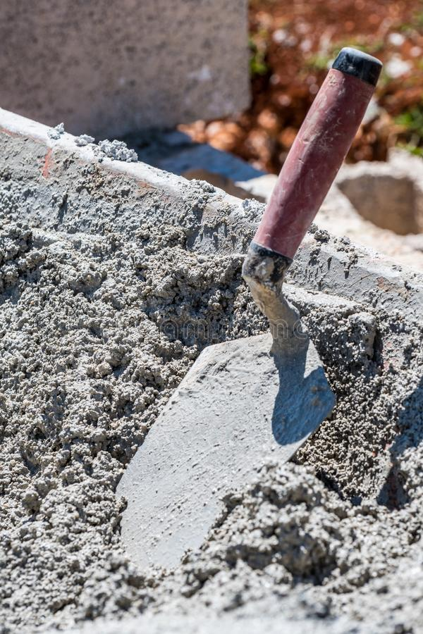 Mixed wet cement in wheelbarrow with trowel stock images