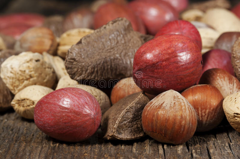 Mixed Whole Nuts. Grouping of mixed whole nuts including pecans, brazils, almonds and hazelnuts all in their shells on wooden surface stock photography