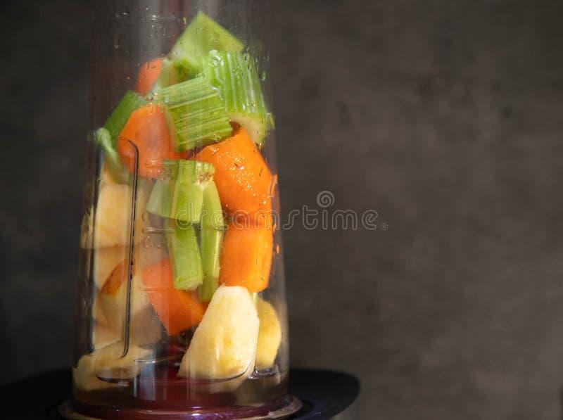 Mixer met Verse Groenten Gesneden selderie, appel en wortel in een mixerkop voor een smoothie Gezond voedsel Ruw voedsel grijs stock afbeelding