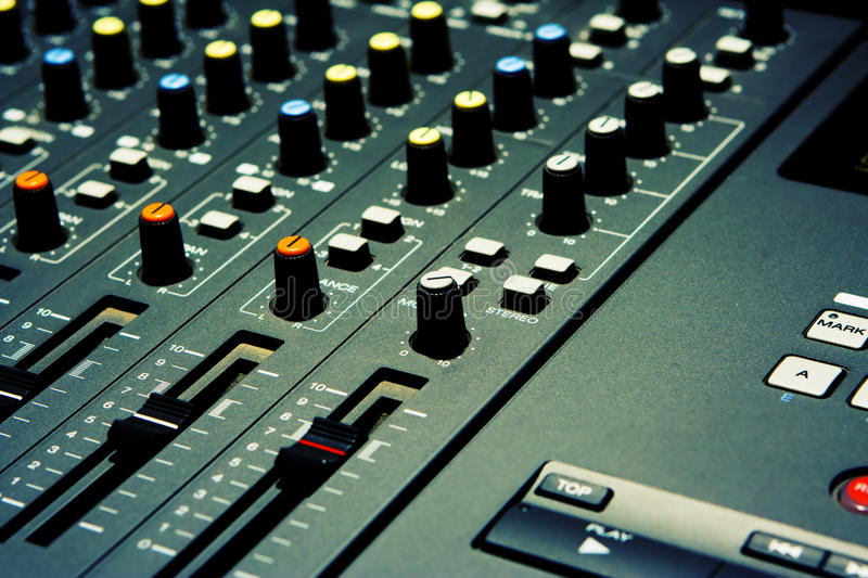 Mixer - The Musical Kind. Closeup of a mixer on a four track digital recorder. Real dirt and dust give this image a gritty vintage feel. Shallow depth of field stock image