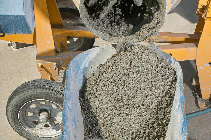Mixer pouring wet cement into wheelbarrow close up. A close up image of an electric concrete mixer pouring wet cement into wheelbarrow stock photo