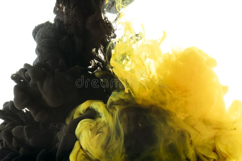 Mixing of black and yellow paint,. Isolated on white royalty free stock photo