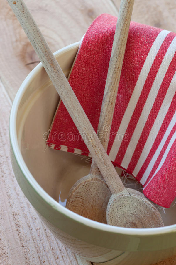 Mixing bowl with spoons and towel. A green ceramic mixing bowl holds two wooden cooking spoons and a red striped towel royalty free stock photo