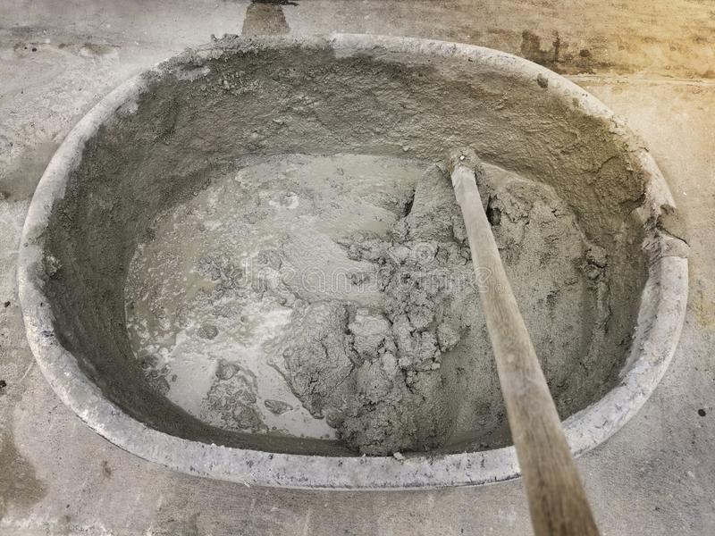 Mixing cement, sand, stone in the basin for mixing. For design stock photo