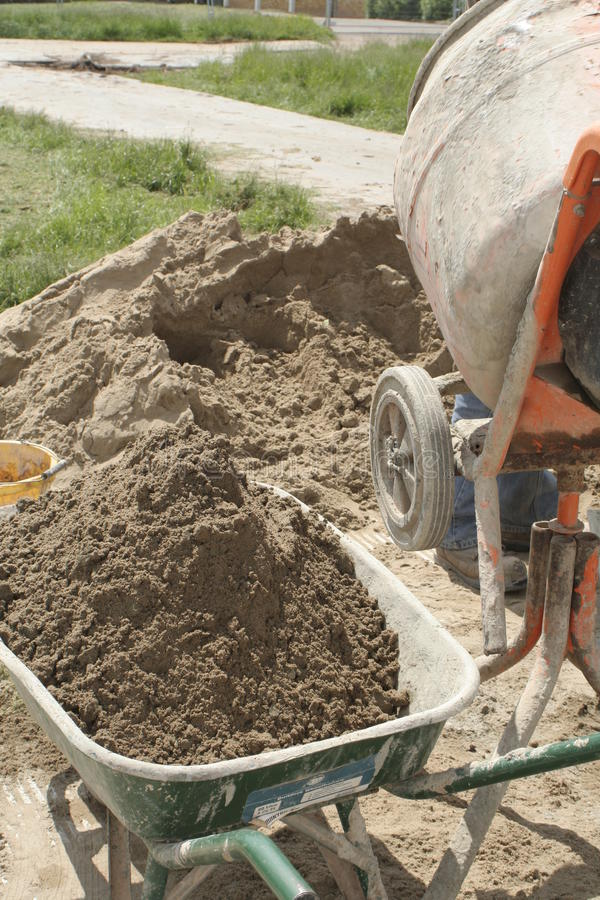 Mixing cement. Sand in a wheelbarrow or cart for use with the cement mixer in construction or trade abstract and concept stock photography