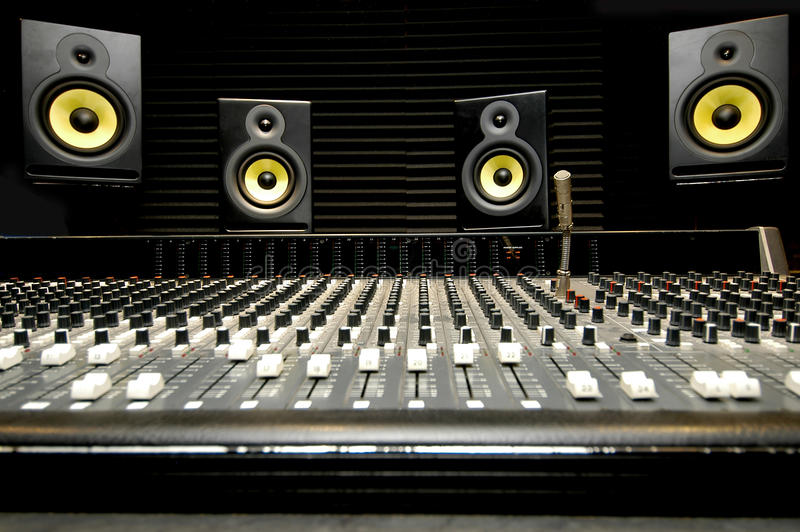 Mixing desk with speakers. Low angle shot of a mixing desk with yellow and black speakers royalty free stock images