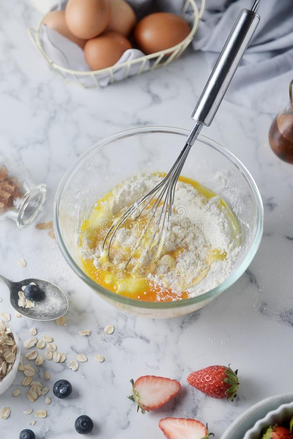 Mixing eggs and flour in bowl. Concept of Cooking ingredients and method on white marble background, Dessert recipes. Mixing eggs and flour in bowl. Concept of stock photography