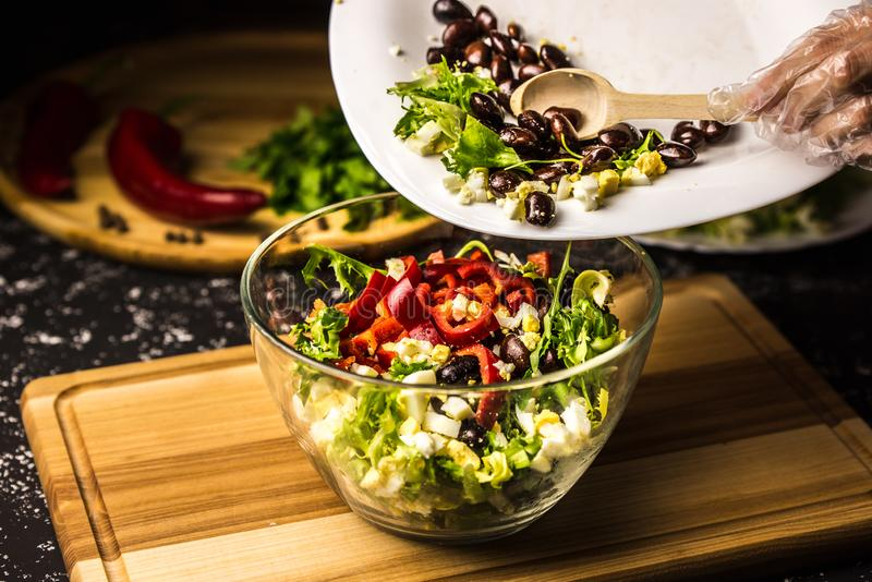 Mixing the ingredients of black bean salad, lettuce, eggs and sweet pepper in a glass bowl royalty free stock photos