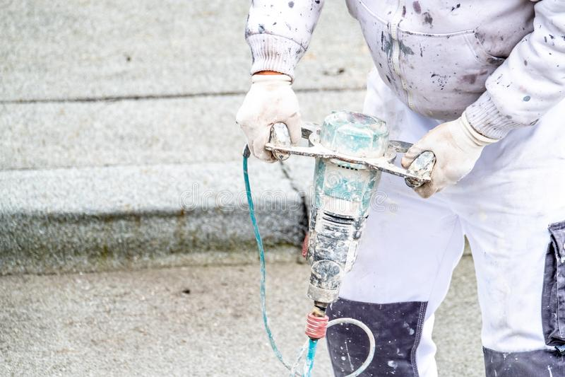 Mixing plaster solution in a bucket, using an electric drill stock photo
