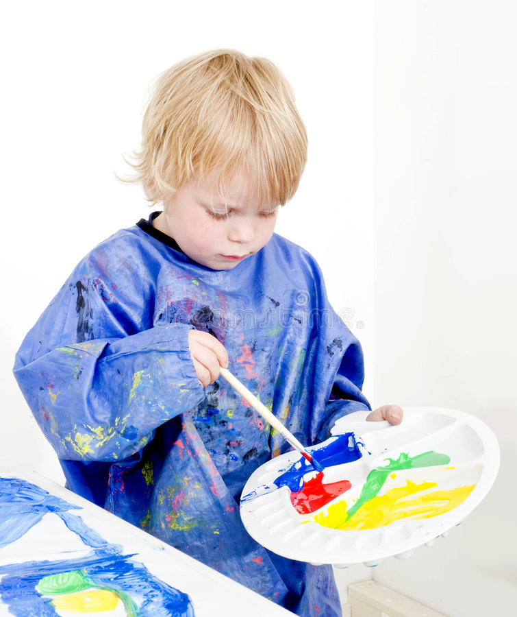 Mixing poster paint. A young boy with a palette in his hand mixing poster paint with a brush royalty free stock photos