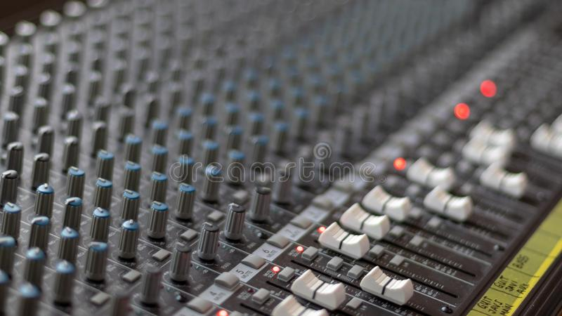 Mixing table with buttons and volume controls and red lights. Music and radio studio stock image