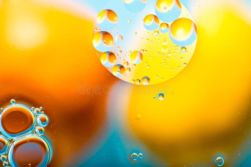 Mixing water and oil, beautiful color abstract background based on red and yellow circles and ovals, macro abstraction. Abstract colorful backdrop with oil drops stock photo