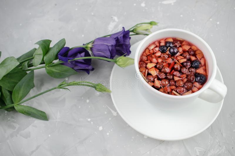 Mixture herbal floral tea with petals, dry berries and fruits. healthy drink. Hot fruit, healthy tea in a white mug.  royalty free stock photography