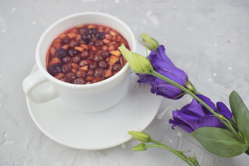 Mixture herbal floral tea with petals, dry berries and fruits. healthy drink. Hot fruit, healthy tea in a white mug.  royalty free stock photos