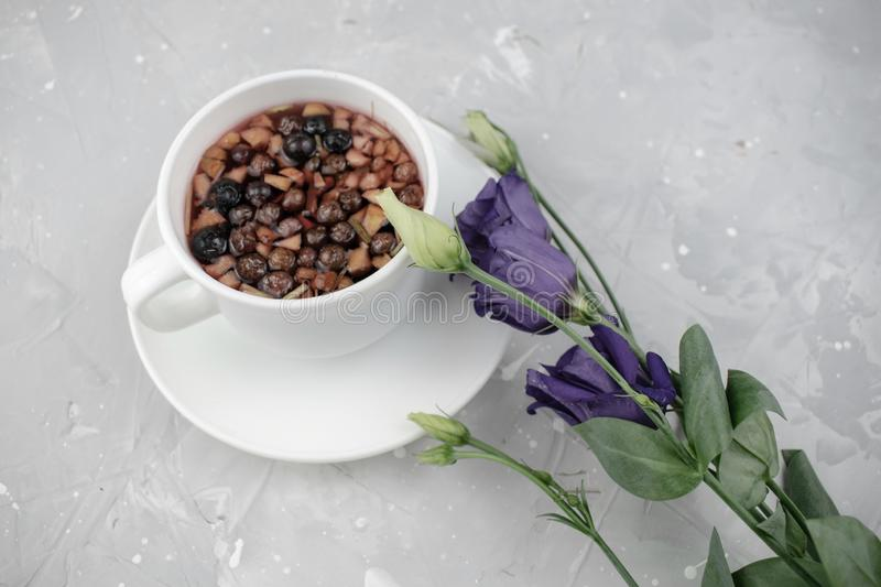 Mixture herbal floral tea with petals, dry berries and fruits. healthy drink. Hot fruit, healthy tea in a white mug.  stock photos