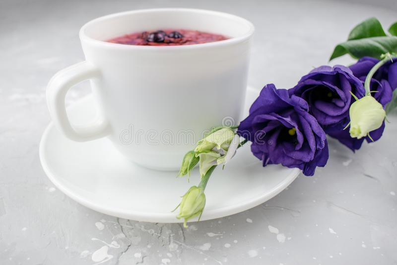 Mixture herbal floral tea with petals, dry berries and fruits. healthy drink. Hot fruit, healthy tea in a white mug.  stock images