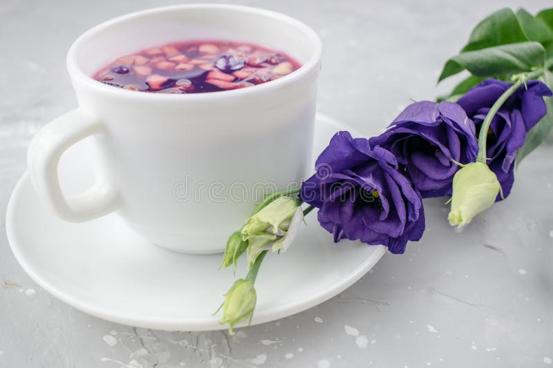 Mixture herbal floral tea with petals, dry berries and fruits. healthy drink. Hot fruit, healthy tea in a white mug.  royalty free stock photo