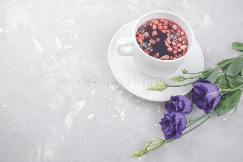 Mixture herbal floral tea with petals, dry berries and fruits. healthy drink. Hot fruit, healthy tea in a white mug.  royalty free stock image