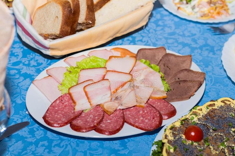 A mixture of sliced meat, sausage and ham, set the restaurant table stock image