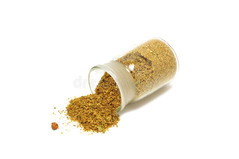 A mixture of spices and herbs in a glass bottle. On a white background royalty free stock photos