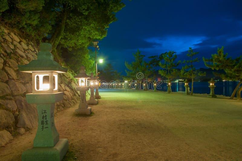 Miyajima island. Path on Miyajima island near Itsukushima shinto shrine, Japan shortly after the sunset with a row of lit lanterns on the shore stock photos