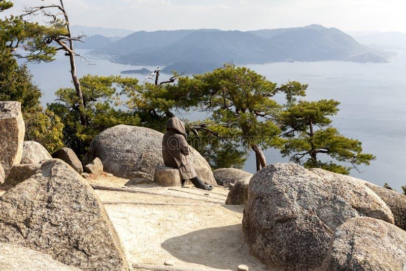 Miyajima, Japão - 28 de dezembro de 2009: Mulher que admira a vista bonita na ilha do mar Miyajima é uma ilha pequena fora da cid imagem de stock