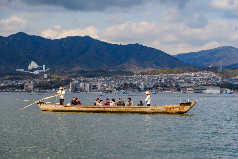 MIYAJIMA, JAPÓN - 3 DE FEBRERO DE 2018: Turistas y locals en un barco con dos hombres japoneses con las paletas que navegan en el fotografía de archivo libre de regalías